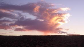 Desert storm illuminated by the setting sun.
